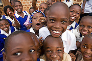 School children happy to finish for the day from a primary school near Kalerwe market, Kampala, Uganda,
