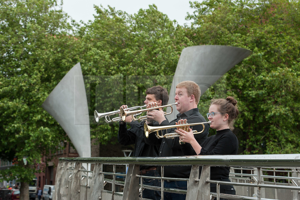 "© Licensed to London News Pictures. 27/07/2015. Bristol, UK.  ""Fanfare for Bristol"", titled ""At the Top of the Tide"", composed by David Mitcham, commissioned by Bristol Proms 2015.  Picture shows trumpeters l-r: Gideon Brooks, Chris Hart, Helen Whitemore, playing on Pero's Bridge in Bristol Harbourside.  The fanfare was performed live for the Mayor of Bristol, George Ferguson and Artistic Director of the Bristol Old Vic, Tom Morris for the first time at Bristol's famous Temple Mead train station, heralding the opening of the Bristol Proms 2015.  David Mitcham's  ""At the Top of the Tide"" was inspired by 'Bristol's inextricable links to the sea'.  The first performance by Arc Brass took place outside the Engine Shed, and throughout the day, performances took place at the Watershed, Pero's Bridge, the Wills Memorial Bell Tower and finally at Bristol Old Vic itself. David Mitcham, who has worked extensively for the BBC Natural History Unit based in Bristol said: ""I am thrilled that my Fanfare ""At the Top of the Tide"" has been chosen for the city of Bristol and to open Bristol Proms 2015. I hope the Fanfare represents the rich diversity of Bristol, its maritime and industrial heritage as well as being a celebration of the spirit of the city and the energy it will carry into the future.""  Bristol Proms 2015 runs from today, 27th July to 1st August and features some of the world's finest musicians including Alison Balsom, Miloš Karadaglić, Pumeza Matshikiza and Daniel Hope.  Photo credit : Simon Chapman/LNP"