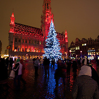 The Christmas tree in the center of the Grand Place, as the Town Hall is painted red with light