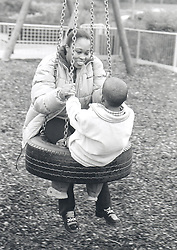 Mother and young son playing on tyre swing in children's playground,