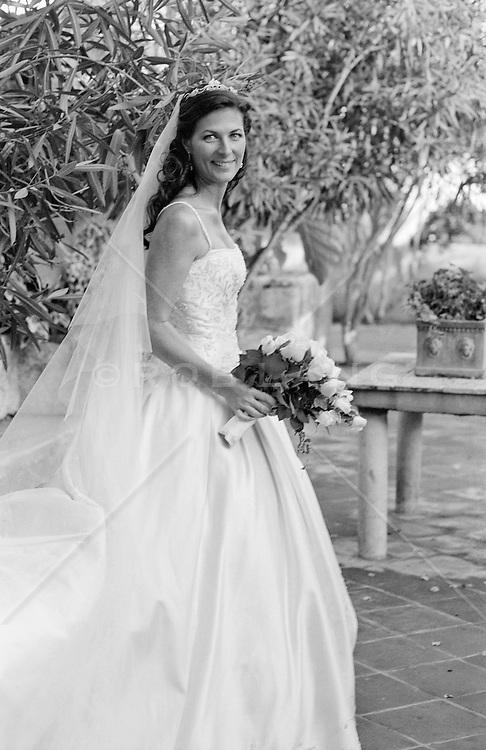 Bride walking outdoors carrying flowers