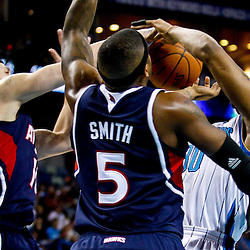 December 26, 2010; New Orleans, LA, USA; New Orleans Hornets power forward David West (30) is fouled by Atlanta Hawks point guard Mike Bibby (10) as power forward Josh Smith (5) defends during the second quarter at the New Orleans Arena.  Mandatory Credit: Derick E. Hingle