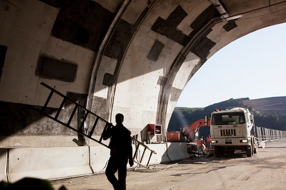 Bagnara, Italy - 18 July, 2012: A worker carries a ladder on the construction site of the Sfalassà bridge on 18 July, 2012, in Bagnara, Italy. The Autostrada A3 Salerno-Reggio Calabria is a motorway in the south of Italy, which runs from Salerno to Reggio Calabria via Salerno. Due to its notorious poor conditions of maintenance, and its difficult route, the motorway has been often taken as a symbol of the backwardness and economical problems of southern Italy.