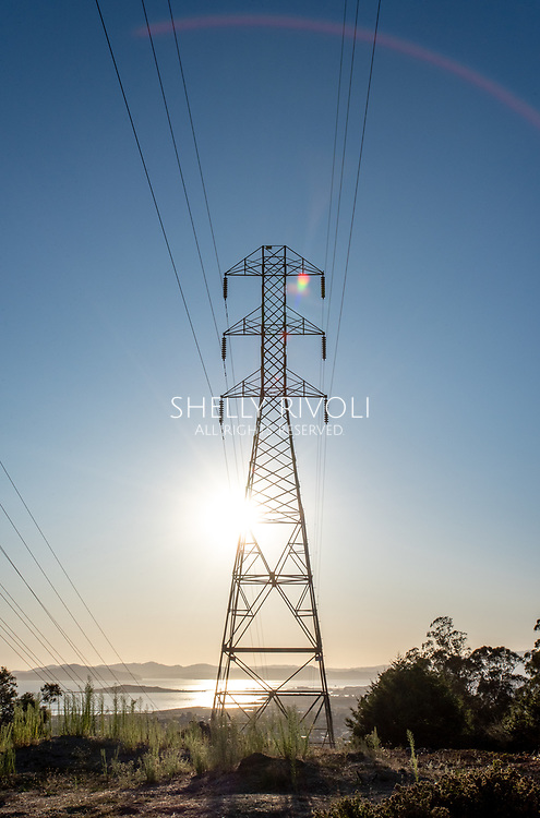 Transformer tower with power lines and view of San Francisco Bay, rainbow sun flare.