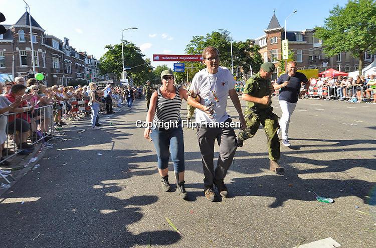 Nederland, Nijmegen, 21-7-2017Intocht van de wandelaars in Nijmegen op de vierde dag van de 101e 4Daagse . Het vierdaagselegioen loopt over de Via Gladiola Nijmegen binnen. vlak voor de deadline van 18.00 uur komen nog mensen aan op de Wedren, uitgeput maar blij.  Na een feestelijke intocht volgt de uiteindelijke finish en het ophalen van het kruisje, vierdaagsekruisje, op de Wedren. Iedere deelnemer krijgt een bloem, gladiool, uitgerijkt. Foto: Flip Franssen