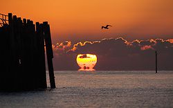© Licensed to London News Pictures. 06/11/2017. Southsea, UK.  The sun appears to melt on the horizon as it rises over the English Channel this morning, 6th November 2017. Photo credit: Rob Arnold/LNP