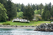 The former Fluke family vacation home greets public visitors in a small bay on the northwest side of Vendovi Island, Skagit County, Washington, USA. Vendovi Island was named after a Fijian High Chief Ro Veidovi who was brought to North America by the 1841 Wilkes Expedition. The San Juan Preservation Trust, a land trust for conservation in the San Juan Islands, purchased the island in December 2010 from the family of John Fluke Sr. Vendovi Island lies across Samish Bay from mainland Skagit County, between Guemes Island and Lummi Island, in the Salish Sea.