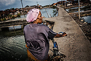 An elderly woman takes her bike walk on the elevated road in Bedono village, near Semarang.