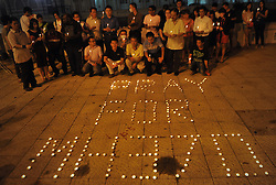 Malaysians pose behind a slogan 'Pray for MH370' made of candles during a vigil for the missing Malaysia Airlines passengers in Kuala Lumpur, Malaysia, March 10, 2014. Malaysia Airlines flight MH370 with 239 people on board went missing early 08 March 2014 while on its way to Beijing, China. Malaysia will expand search and rescue operations to locate the missing Malaysia Airlines passenger jet with 239 people on board, as the third day of searching yielded no results, a senior Malaysian aviation official said,  Monday, 10th March 2014. Picture by Mohd FIrdaus / i-Images