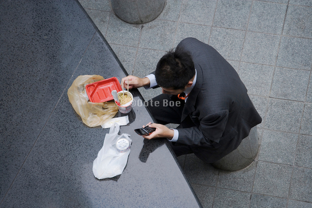 overhead view of Asian person having a lunch while also text messaging