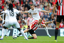 Sebastian Larsson of Sunderland is tackled by Gylfi Sigurosson of Swansea City - Photo mandatory by-line: Rogan Thomson/JMP - 07966 386802 - 27/08/2014 - SPORT - FOOTBALL - Sunderland, England - Stadium of Light - Sunderland v Swansea City - Barclays Premier League.