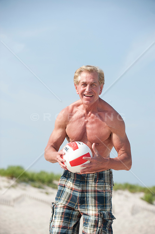 Muscular older man at the beach playing volleyball
