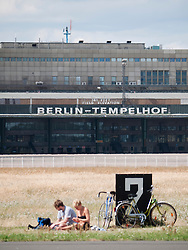 People having picnic next to runway at new city public Tempelhofer Park on site of famous former Tempelhof Airport in Berlin Germany