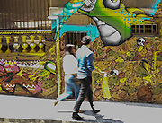 Pedestrians walk past a colorful wall in the hilltop neighborhood of Cerro Alegre, Valparaiso. The ubiquitous street art is a major tourist attraction.