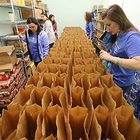 Holly Whitehead, a Junior Auxiliary of Tupelo member, works with other members to fill bags with snacks as part of the Junior Auxiliary's Silent Servings program on Friday morning in Tupelo. The Silent Servings bags are for area students lacking nutritional support at home and are packed every two weeks then picked up by a school employee and also delivered to the schools by a Junior Auxiliary member. The program allows the students to have snack over the weekend that they may otherwise not get.