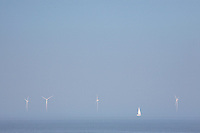 Sailing ship in wind farm in ocean