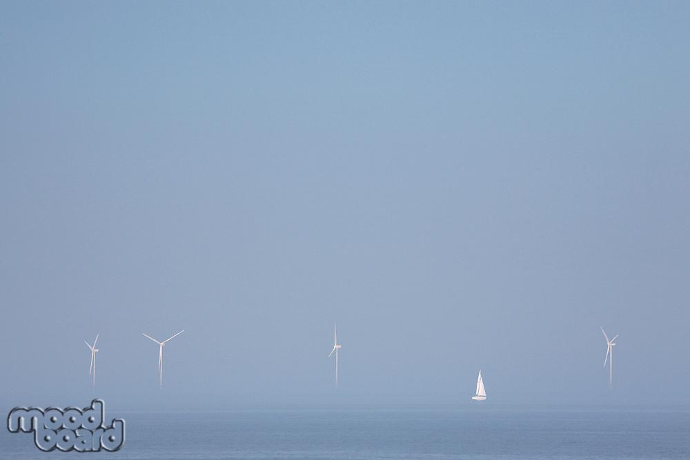 Sailing ship in wind farm in ocean