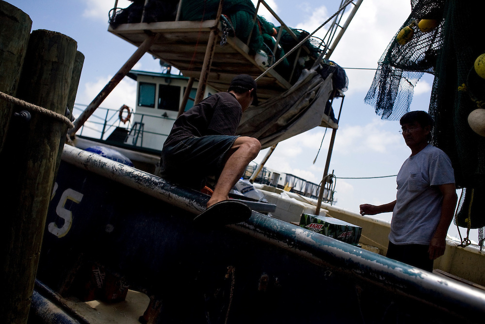 From left, Hung Tran, 42, and Roi-van Nguyen, 63, load the H&R shrimp boat at Dean Blanchard Seafood, Inc. in Grand Isle, LA on June 24, 2010 where a fishing ban has been put in place due to the B.P. oil spill. The H&R crew will head west in hopes to find open fishing waters after waiting two months for B.P. to hire their boat.