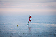 Marker buoy floating in the sea with flags attached to show a location of a Lobster or crab pot Hythe Bay, the English Channel, United Kingdom.  (photo by Andrew Aitchison / In pictures via Getty Images)