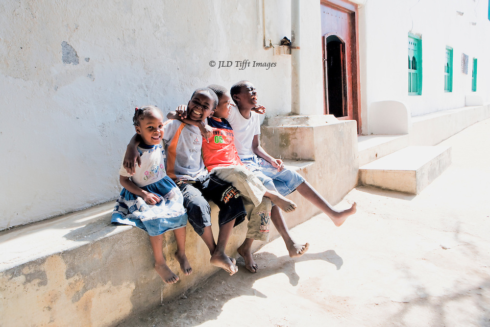 Oman, in the village of Mirbat.  Four laughing children seated together on a bench outside one of the village houses.