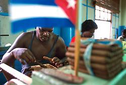 Workers hand roll cigars at the La Corona factory in Havana, Cuba. (Photo © Jock Fistick)