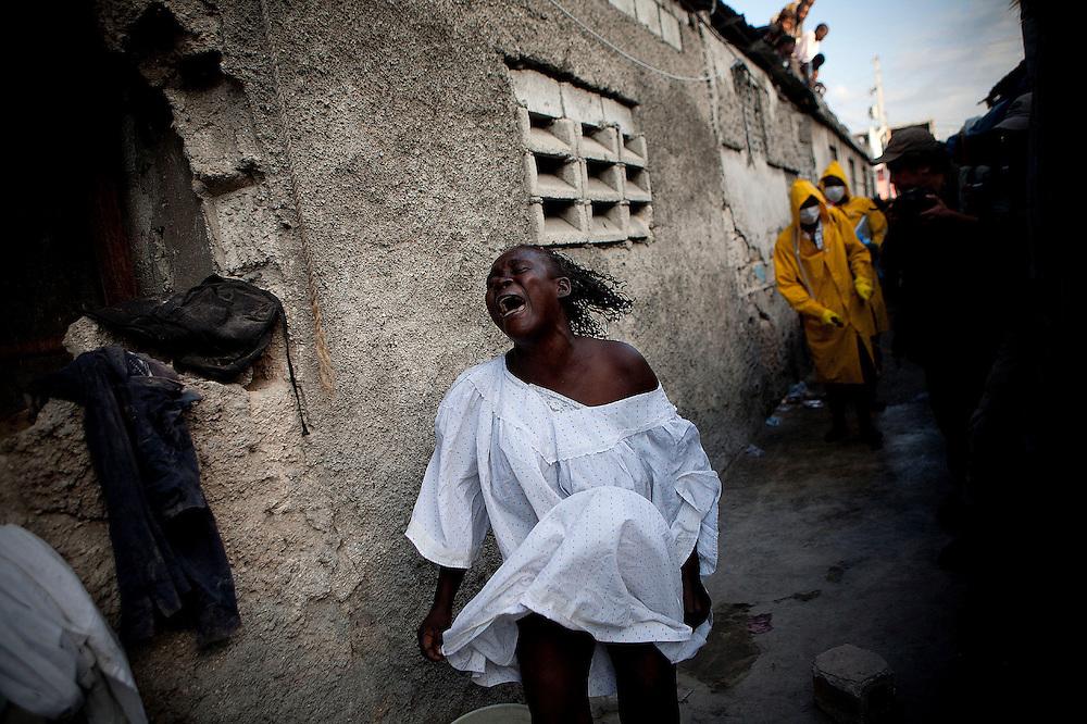 Durante la segunda quincena del mes de Octubre de 2010 comenzaron a aparecer casos de C&oacute;lera en la regi&oacute;n de Artibonite, en Hait&iacute;. Desde entonces la epidemia ha dejado m&aacute;s de 4.500 muertos y cerca de 250.000 afectados.<br /> <br /> A woman screams as workers of Haiti's Health Ministry arrive to her house to pick up her daughter's body, who died for cholera, and bury it in a mass grave on the outskirts of Port-au-Prince. Two cars from the Morgue had came before to pick up the body, but only this team was able to do it, and disinfect the place. <br /> <br /> <br /> Andr&eacute;s Mart&iacute;nez Casares/EFE