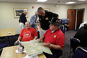 Scout pilots: Ray Arnold, B Troop, left, and Chuck Kenny, center, look at B Troop slick pilot John Flanagan's map which was returned after over 40 years. Gathering of Warriors reunion attended by Vietnam War Veterans of the 1st Squadron, 9th Cavalry, 1st Cavalry Divison.