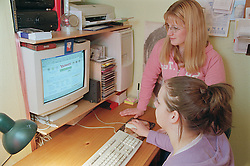 Two teenage girls sitting at desk using computer,
