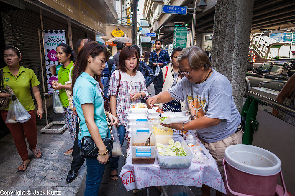 "20 MAY 2104 - BANGKOK, THAILAND:  Thai office workers in Bangkok buy their lunch from a street vendor after the army declared martial law. The Thai Army declared martial law throughout Thailand in response to growing political tensions between anti-government protests led by Suthep Thaugsuban and pro-government protests led by the ""Red Shirts"" who support ousted Prime Minister Yingluck Shinawatra. Despite the declaration of martial law, daily life went on in Bangkok in a normal fashion. There were small isolated protests against martial law, which some Thais called a coup, but there was no violence.   PHOTO BY JACK KURTZ"