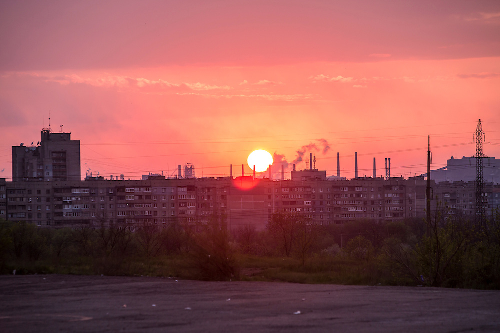 LUHANSK, UKRAINE - MAY 3: The sun sets behind apartment blocks and factory smokestacks on May 3, 2014 near Lukansk, Ukraine. Cities across Eastern Ukraine have been overtaken by pro-Russian protesters in recent weeks, leading the Ukrainian military to respond with force in some areas. (Photo by Brendan Hoffman for The Washington Post)