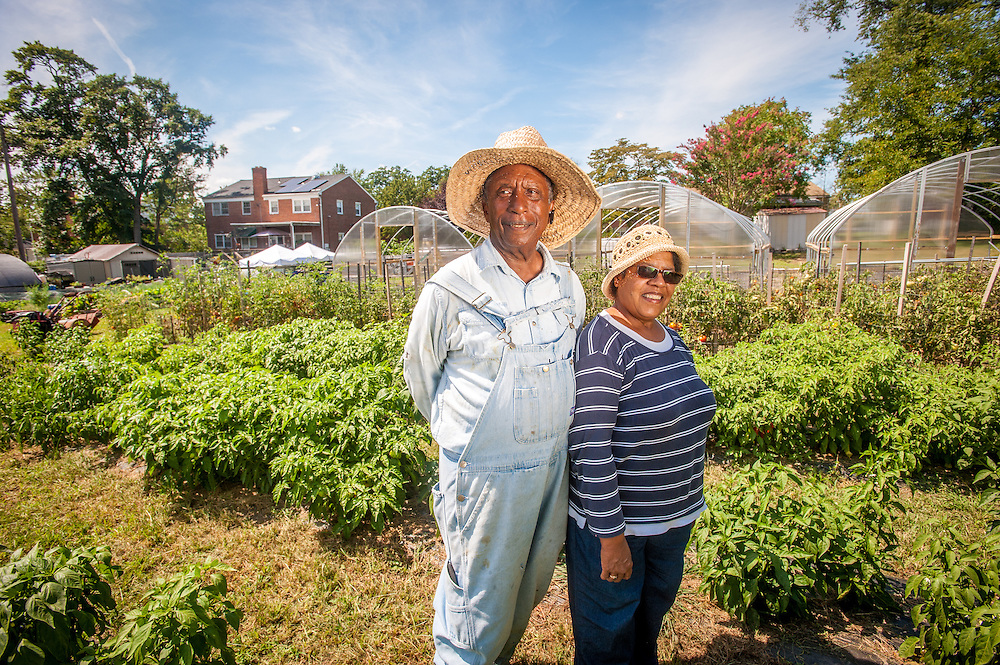 An African American couple pose together on their urban vegetable garden property located in Baltimore city, Maryland.