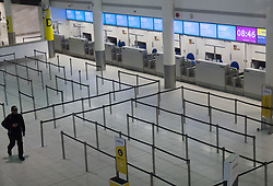 © Licensed to London News Pictures. 02/10/2017. Crawley, UK. A passenger walks past unattended Monarch Airlines check-in desks at Gatwick Airport after the airline ceased trading at midnight last night. The government has announced that it will start the country's biggest ever peacetime repatriation to fly about 110,000 stranded passengers home. Photo credit: Peter Macdiarmid/LNP