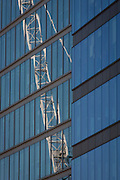 Reflection of a construction crane with existing corporate office windows in the City of London, UK.