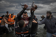A volunteer holds up a baby as others help migrants and refugees to disembark from a dinghy after their arrival from the Turkish coast to the Greek island of Lesbos, Wednesday, Nov. 25, 2015. About 5,000 migrants reaching Europe each day over the so-called Balkan migrant route. The refugee crisis is stoking tensions among the countries on the so-called Balkan migrant corridor — Greece, Macedonia, Serbia, Croatia and Slovenia. (AP Photo/Santi Palacios)