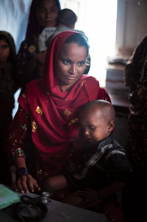 Hamida Haji Hasbeeb with her son Hasbeeb visits the Government Health Clinic in the village of Babrio Jat, Thatta, Sindh, Pakistan on July 2, 2011. She is 7 months pregnant and has two children. Visting for advice on nutrition.