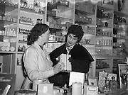 "Mr Eamon Andrews and Alma Cogan at Woulfes Pharmacy, Grafton St.01/12/1954..Alma Cogan (19/05/1932 – 26/10/1966) was an English singer of traditional pop music in the 1950s and early 1960s. Dubbed ""The Girl With the Laugh/Giggle/Chuckle In Her Voice"", she was the highest paid British female entertainer of her era. Throughout the mid-1950s, she was the most consistently successful female singer in the UK."