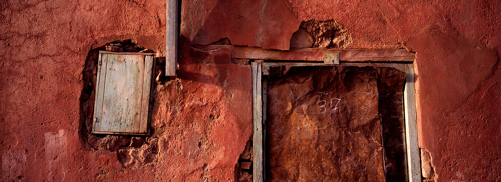 Ancient red wall with doorway, number 37