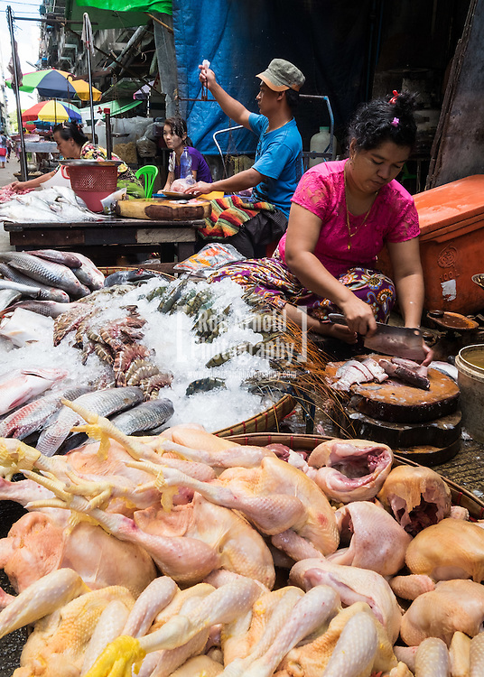 A woman chopping fresh fish at a street market stall in Downtown Yangon.