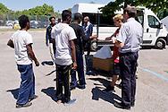 Roma 12 maggio 2015<br /> Il giorno dopo lo sgombero  dell'insediamento  nei pressi della stazione della metropolitana di Ponte Mammolo, abitato da circa 400 migranti, per lo più richiedenti asilo e rifugiati di Eritrea e di alcune famiglie ucraine, circa 250 persone  rimaste senza casa vivono nel parcheggio vicino alle case distrutte senza nessuna assistenza dalle istituzioni. Sacerdote con alcuni volontari distribuisce viveri ai migranti.<br /> Roma, Italy. 12th May 2015 <br /> The day after the evacuation of the settlement near the Ponte Mammolo metro station,inhabited by about 400 migrants, most asylum seekers and refugees to Eritrea and some Ukrainian families, about 250 people left homeless are living in the parking lot near the destroyed homes without any assistance from the institutions. Priest with volunteers distributing food to migrants.