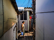 """20 JUNE 2017 - BANGKOK, THAILAND:  A woman walks to the river to bathe in a community along the Chao Phraya River south of Krung Thon Bridge. This is one of the first parts of the riverbank that is scheduled to be redeveloped. The communities along the river don't know what's going to happen when the redevelopment starts. The Chao Phraya promenade is development project of parks, walkways and recreational areas on the Chao Phraya River between Pin Klao and Phra Nang Klao Bridges. The 14 kilometer long promenade will cost approximately 14 billion Baht (407 million US Dollars). The project involves the forced eviction of more than 200 communities of people who live along the river, a dozen riverfront  temples, several schools, and privately-owned piers on both sides of the Chao Phraya River. Construction is scheduled on the project is scheduled to start in early 2016. There has been very little public input on the planned redevelopment. The Thai government is also cracking down on homes built over the river, such homes are said to be in violation of the """"Navigation in Thai Waters Act."""" Owners face fines and the possibility that their homes will be torn down.              PHOTO BY JACK KURTZ"""