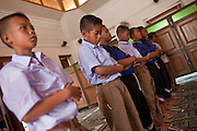 "Sept. 24, 2009 -- PATTANI, THAILAND: Thai schoolboys pray in the Krue Se Mosque in Pattani, Thailand. The Krue Se Mosque is one of Thailand's most historic mosques and long a flash point in Muslim - Buddhist confrontation. The mosque was first destroyed by advancing Thais when Pattani was an independent kingdom in 1786. It was restored in the 1980's but heavily damaged by rockets fired by unknown assailants in 2005. It has since been partially restored by local Muslims and the Thai government. Thailand's three southern most provinces; Yala, Pattani and Narathiwat are often called ""restive"" and a decades long Muslim insurgency has gained traction recently and nearly 4,000 people have been killed since 2004. The three southern provinces are under emergency control and there are more than 60,000 Thai military, police and paramilitary militia forces trying to keep the peace battling insurgents who favor car bombs and assassination.    Photo by Jack Kurtz / ZUMA Press"
