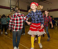 "Bandanas, pigtails and plaid on the dance floor as Janney Halperin ""swings her partner"" Abby Smith during Inter Lakes Elementary School's annual Square Dance on Thursday afternoon.  (Karen Bobotas/for the Laconia Daily Sun)"