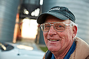 Corn farmer at harvest time, close-up portrait in front of grain bins at sunrise