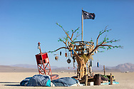 Island of Lost Buoys<br /> by: Lillian Heyward and The Island of Lost Buoys, a Create Change Project<br /> from: Bluffton, SC<br /> year: 2019<br /> <br /> On the playa is an Island, a wooden tree dominates the center made of recycled pallets, crates and drift wood. Leaves of sculpted plastic bottles rustle in the wind. Strung from a branch is a hammock made of fishing net attached to a ocean buoy marooned on the beach. Hanging from the branches are sea buoys and balls providing a place to write names or leave a message to those who will come after.<br /> <br /> Hanging from branches are bamboo wind chimes that softly clatter in the breeze. It is an island, a refuge, a place of calm and childhood in the stormy seas of life. It appears out of the playa as a mirage, the fantasy playground of youth. Discarded materials transform into an oasis, as our adult lives transform back to childhood. Bangarang!<br /> <br /> URL: http://www.createchangeproject.com<br /> Contact: islandoflostbuoys@gmail.com<br /> <br /> https://burningman.org/event/brc/2019-art-installations/?yyyy=&artType=B#a2I0V000001AVsTUAW My Burning Man 2019 Photos:<br />