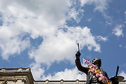 "As a visual pun, the statue of Sir Joshua Reynolds seeminly paints clouds in blue sky from outside the Royal Academy in Piccadilly during the Summer Exhibition, on 13th August 2019, in London, England. This is a new cast of the original that was first exhibited outside the RA in 1904 and is an allegory of the human need for new challenges, of our instinct to always be scanning the horizon and the future. Sir Joshua's statue stands in the ""Annenberg Courtyard"" of Burlington House."