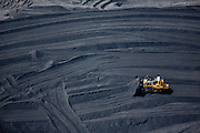 Shoveling piles of tar sands refining byproduct Petroleum Coke