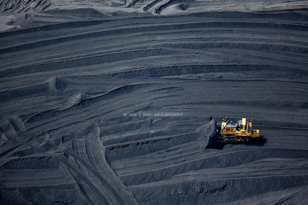 Shoveling piles of tar sands refining byproduct Petroleum Coke