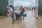 Leaving on foot is slow work - Festival prepare to leave the festival. AA vans have had to pull cars out of the mud and conditions for pedestrians and cars, alike, are very muddy (heavy going) on the morning of the final day of the festival after days of rainy weather.The 2016 Glastonbury Festival, Worthy Farm, Glastonbury.