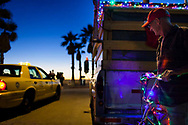 Butch Bauer stands in front of the truck he lives out of in the Pacific Beach community of San Diego, California, December 12, 2010. Bauer decorated his truck and his bike for Christmas.