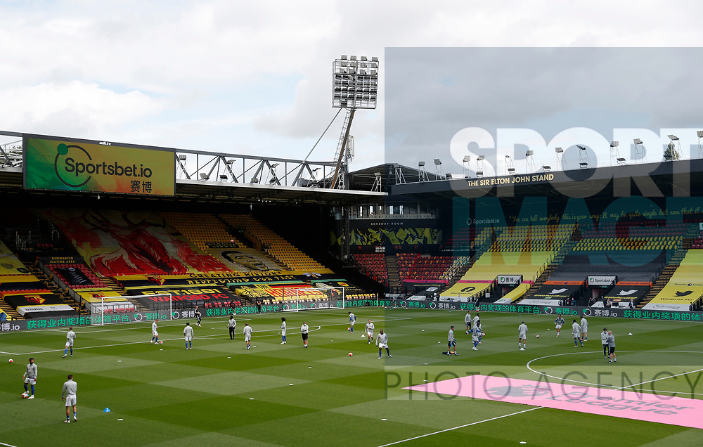 Leicester City players warm up before the giant banners covering the seats where the fans would sit during the Premier League match at Vicarage Road, Watford. Picture date: 20th June 2020. Picture credit should read: Darren Staples/Sportimage